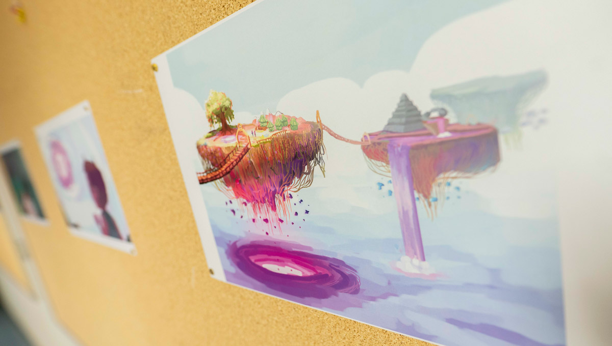Artwork of a floating island from a videogame is posted on a corkboard.