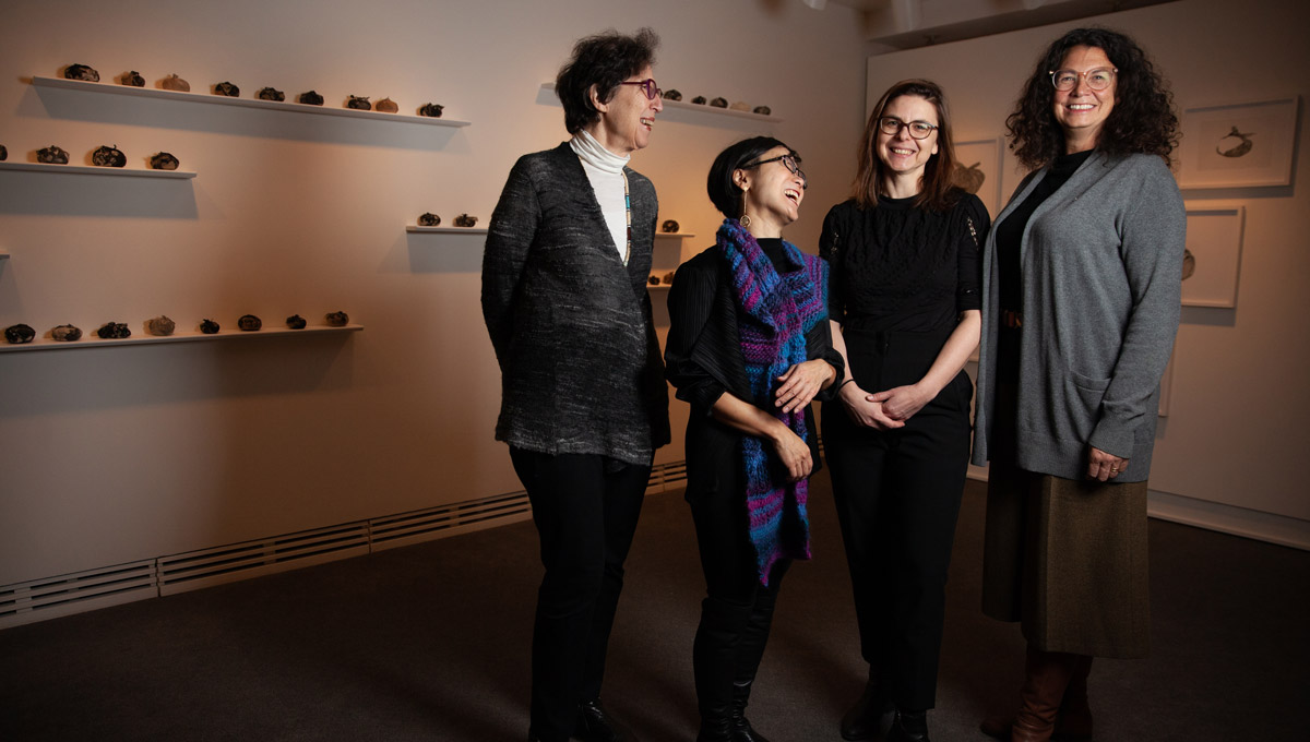 A group of women academics stand together laughing in the Carleton University Art Gallery.