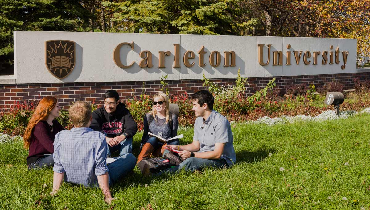 Students, who will benefit from new Carleton programs in 2016 - '17, sit in the grass in front of the Carleton sign at Bronson and Sunnyside.