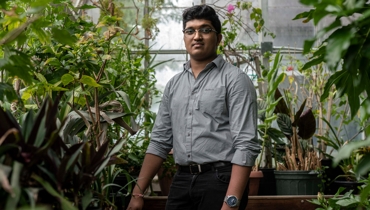 Bhavya Mohan poses in a greenhouse surrounded by plants.
