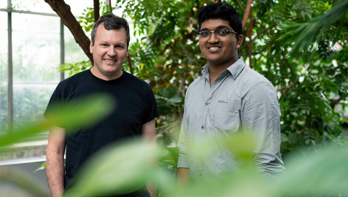 Prof. Bill Willmore and Bhavya Mohan pose in the greenhouse surrounded by plants.