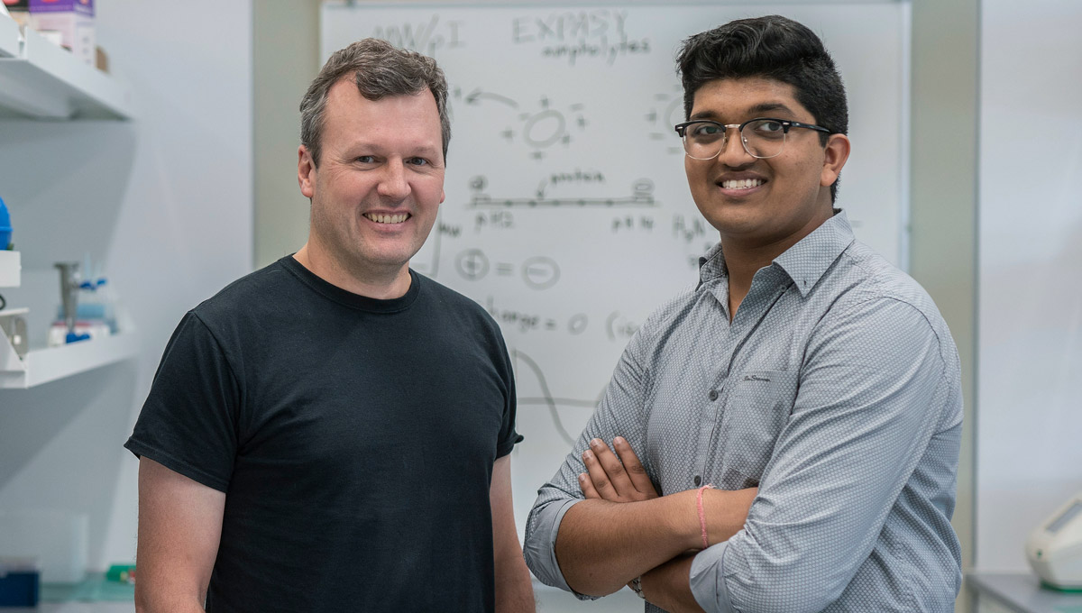 Prof. Bill Willmore and Bhavya Mohan pose in a lab during their science mentorship.