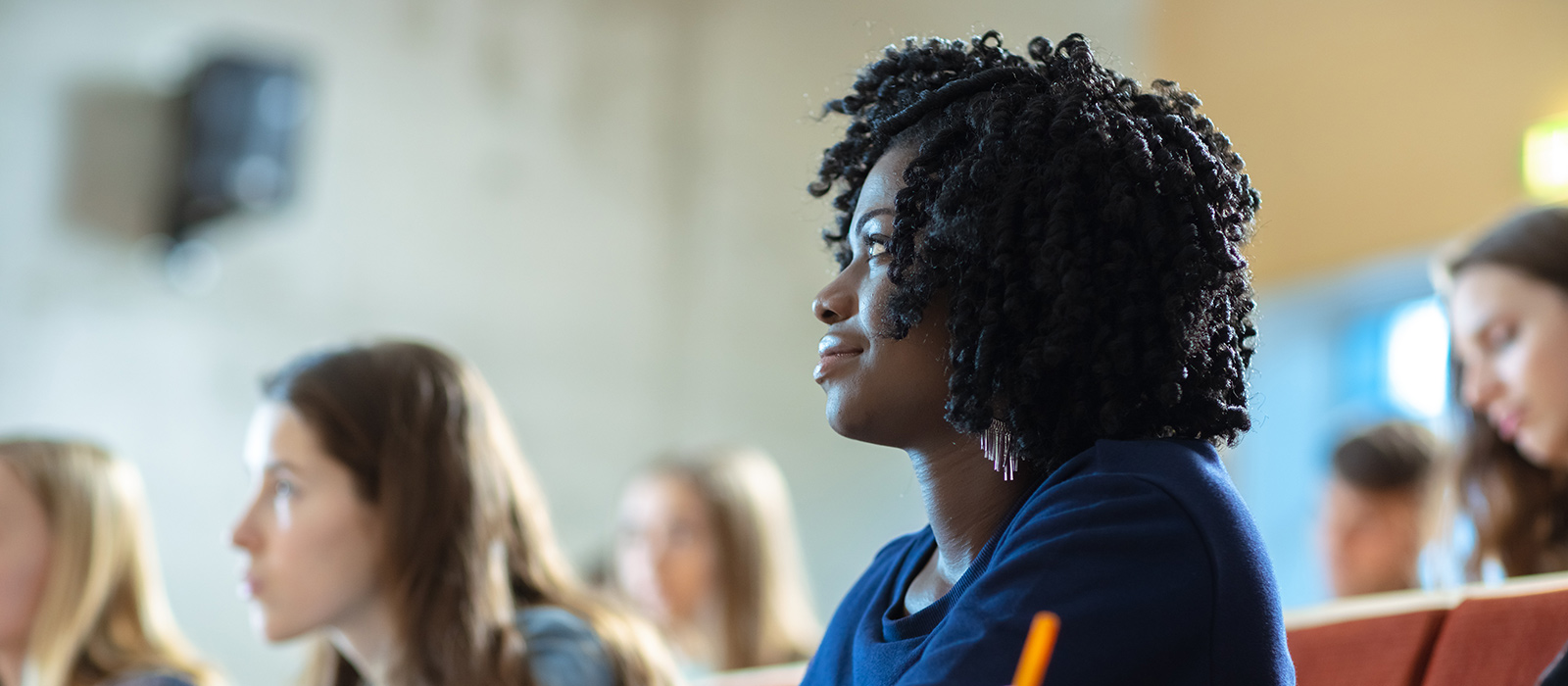 A Black student sitting in a lecture room