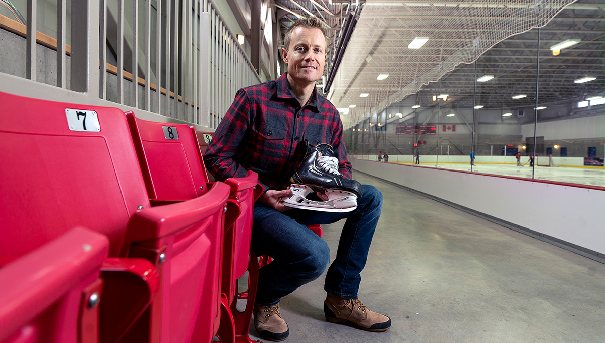 The photo features 'Blade Barber' Tim Maxwell sitting in a skating rink, holding a skate.