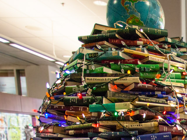 A Christmas tree made of books with a globe on top sits in the MacOdrum Library lobby.