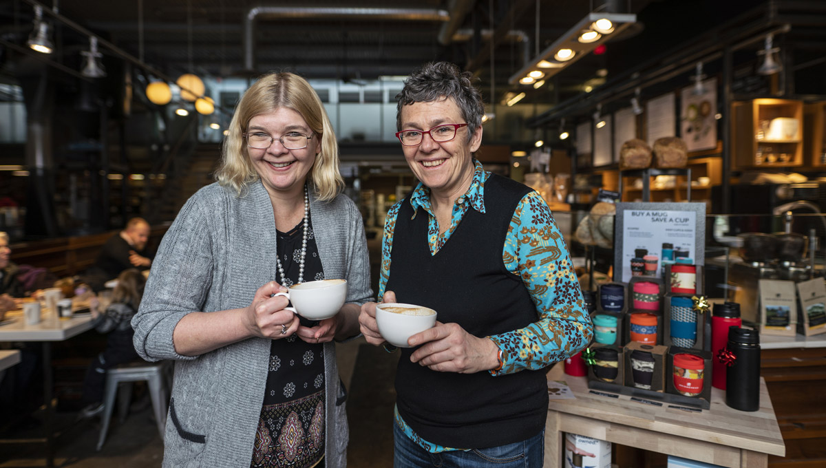 Tracey Clark and Dana Brown pose while holding cups of coffee at a Bridgehead.