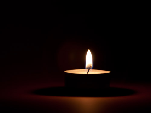 A lit candle against a dark background.