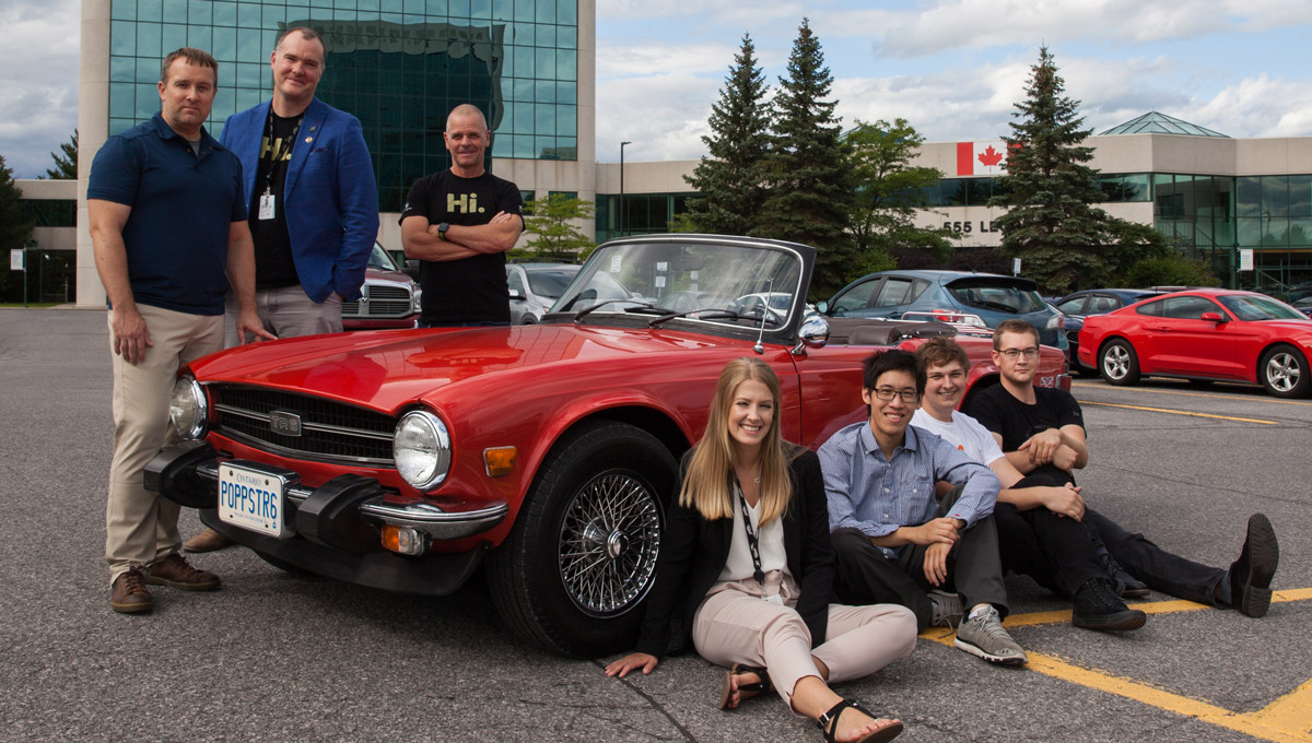 Carleton Canopy Growth interns sit on the ground in front of a red Triumph TR6 car in a parking lot.