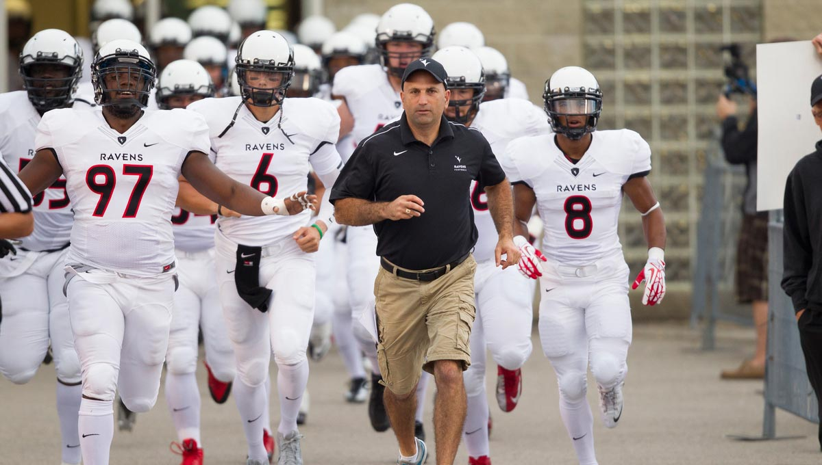Carleton Ravens head coach Steve Sumarah leads the team onto the field before a game.
