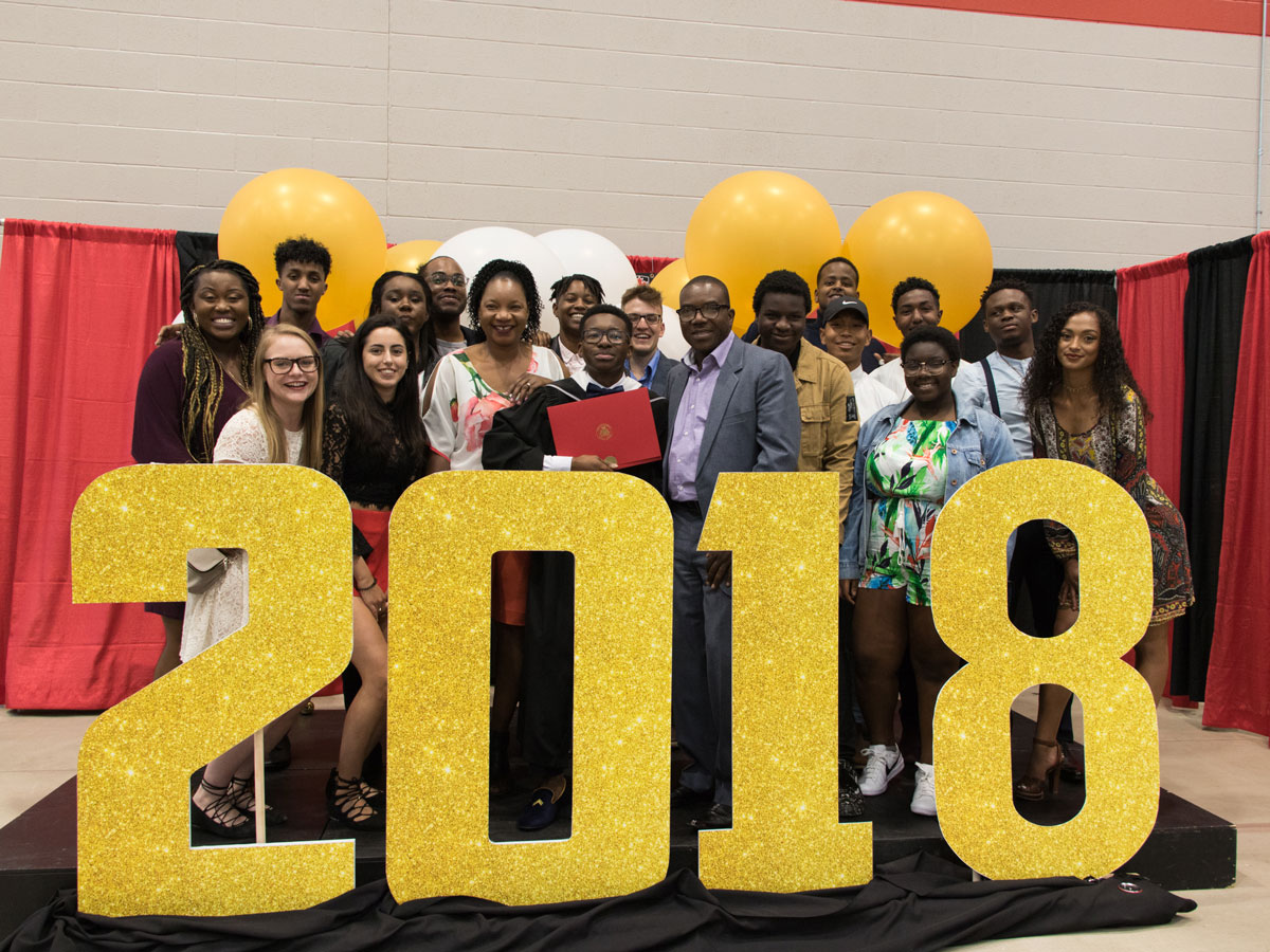 A group of students and their families gather around a large 2018 sign during Carleton University's Convocation.