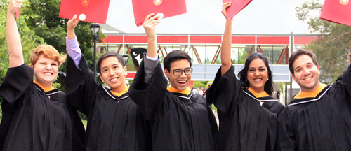 Students hold up their newly-granted degrees in the air while wearing black Convocation robes