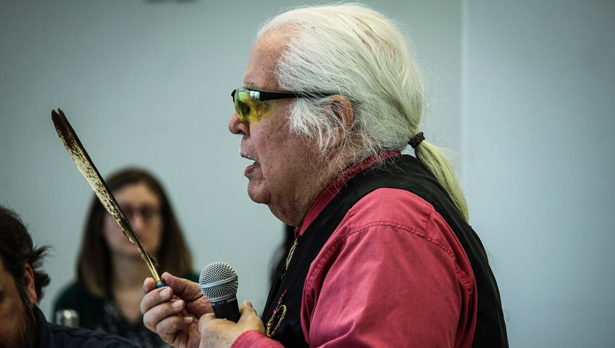 Mohawk Traditional Teacher Paul Skanks holds a feather while speaking to conference attendees.