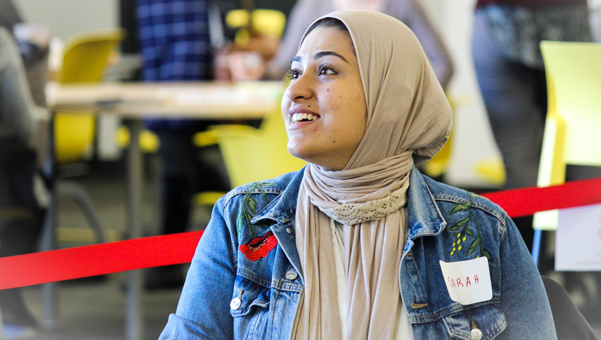 A student in a hijab networks with attendees during the conference.