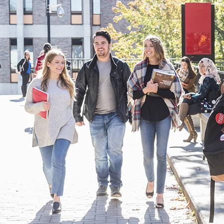 Photo of 3 Carleton students walking through campus.