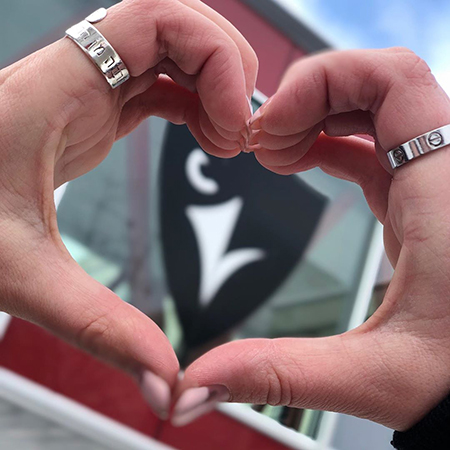 A student makes a heart shape using their fingers while holding it over the Carleton Ravens logo. The optics make it appear as if the Ravens logo is inside the heart.