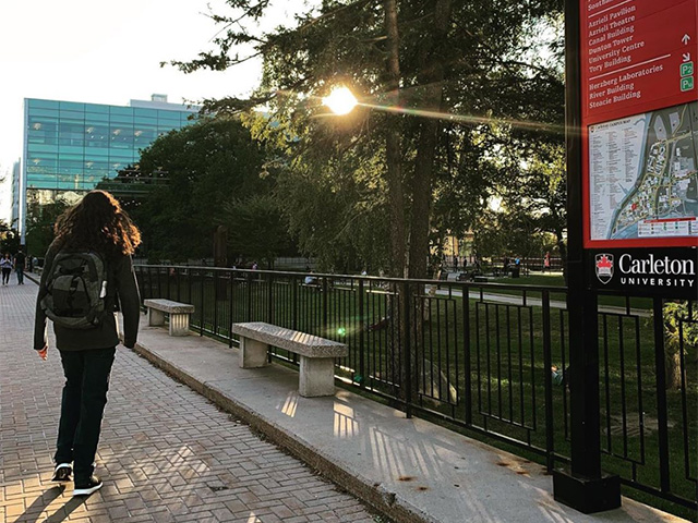 A photo of a Carleton University student walking through campus with the sun glaring in the background.