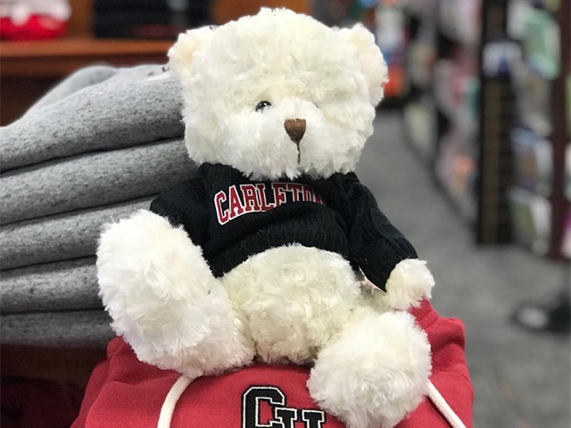 A photo of a white teddy bear wearing a Carleton University t-shirt which is available on campus at the Carleton Bookstore. A red Carleton sweater can be seen under the teddy bear.