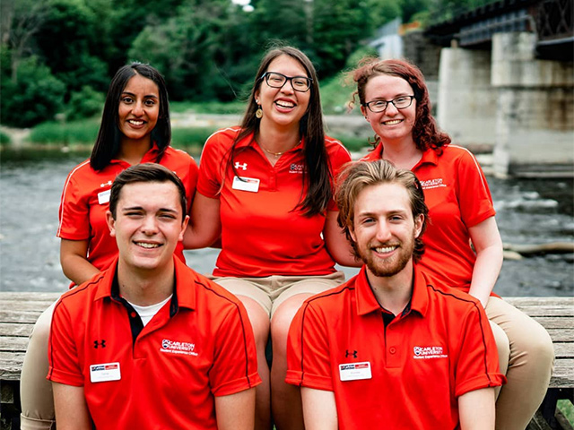 Photo of 5 Carleton University Summer Orientation leaders all wearing the same red shirt, sitting on a bench in front of a river.