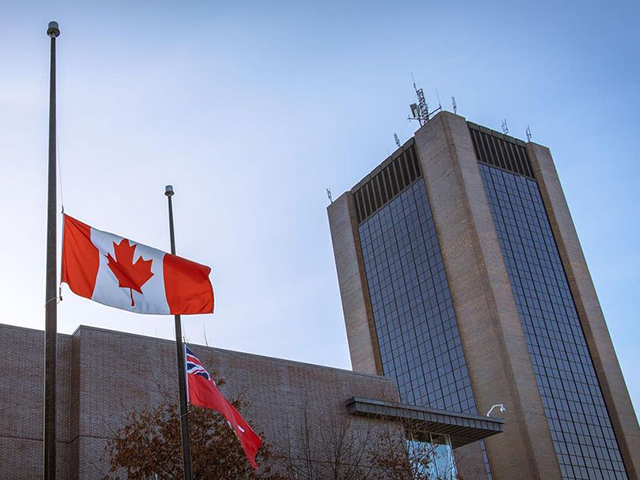 A Canadian flag at half mast with Dunton Tower visible in the background.