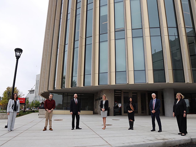 Several members of the Carleton University in front of Dunton Tower