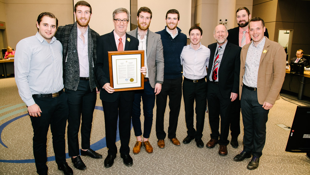 The men's curling team gathers with Mayor Jim Watson and Councillor Mathieu Fleury in council chambers while holding a framed declaration.