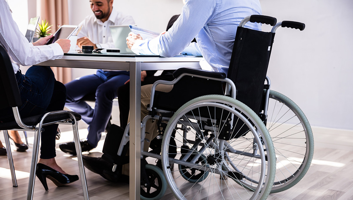 Businessman sitting in a meeting while using a wheelchair