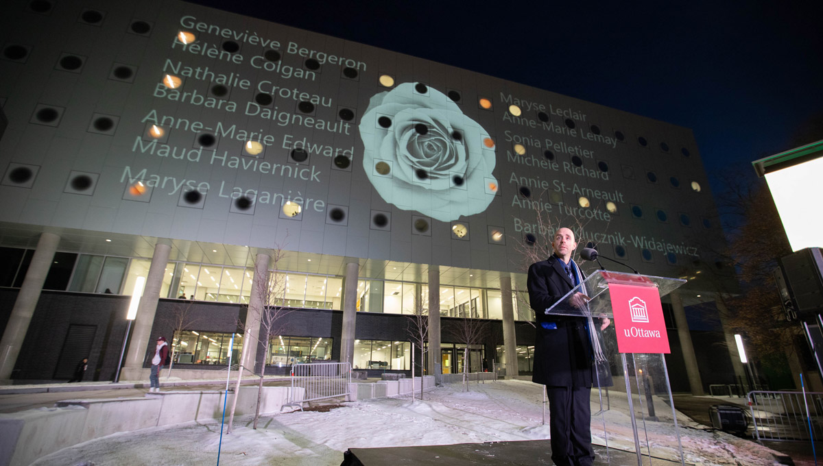 President Benoit-Antoine Bacon speaks at a podium at uOttawa during a vigil commemorating victims of the Montreal Massacre.