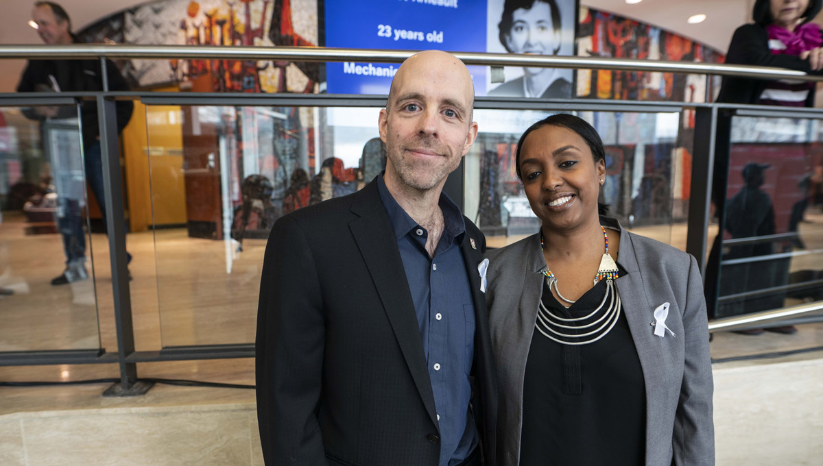 President Benoit-Antoine Bacon and Ikram Jama, Advisor on Human Rights and Equity, stand together in the Tory lobby.