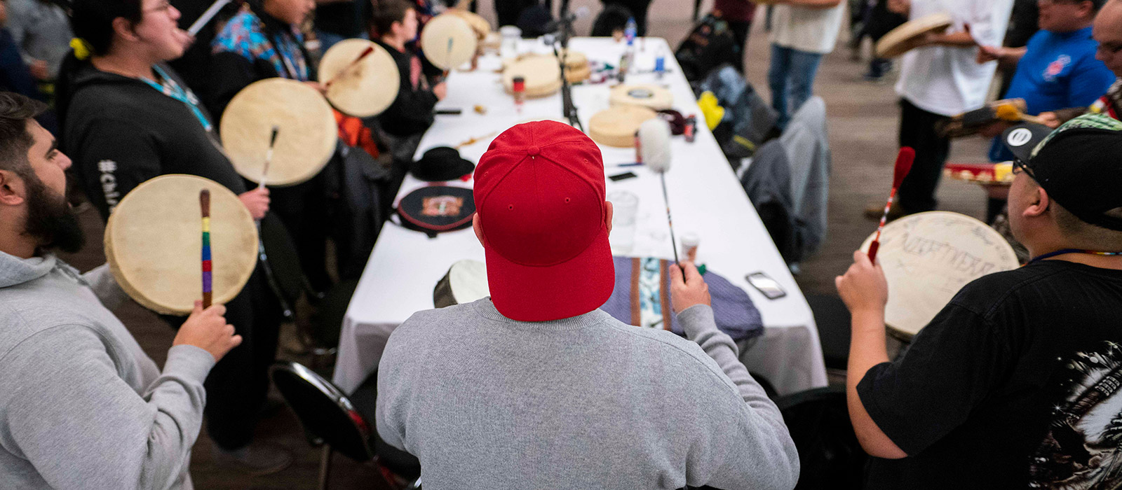 A man wearing a backwards red hat is pictured banging the drums at the Annual Round Dance.