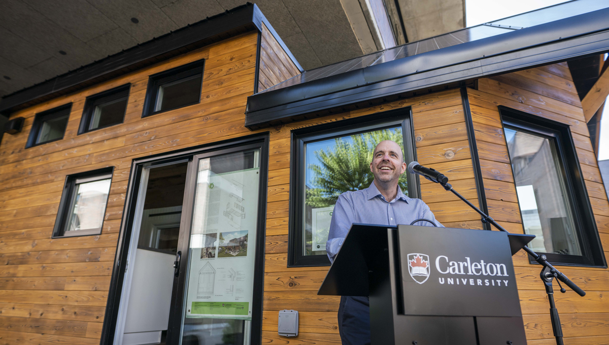 President Benoit-Antoine Bacon speaks at the opening of the Northern Nomad energy autonomous house, which was designed and built by students.