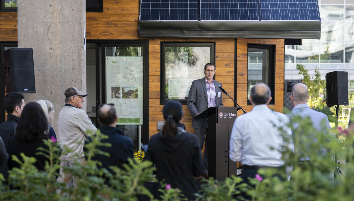 Professor Scott Bucking speaks at the opening of the Northern Nomad energy autonomous house, which was designed and built by students.