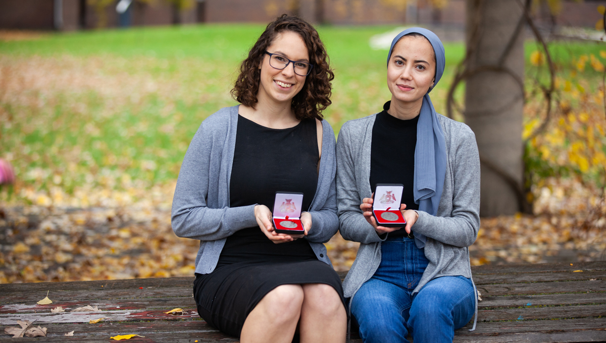 Mercedes Veselka and Samah Saci hold their medals outdoors on a bench in Alumni Park with fallen leaves in the background.