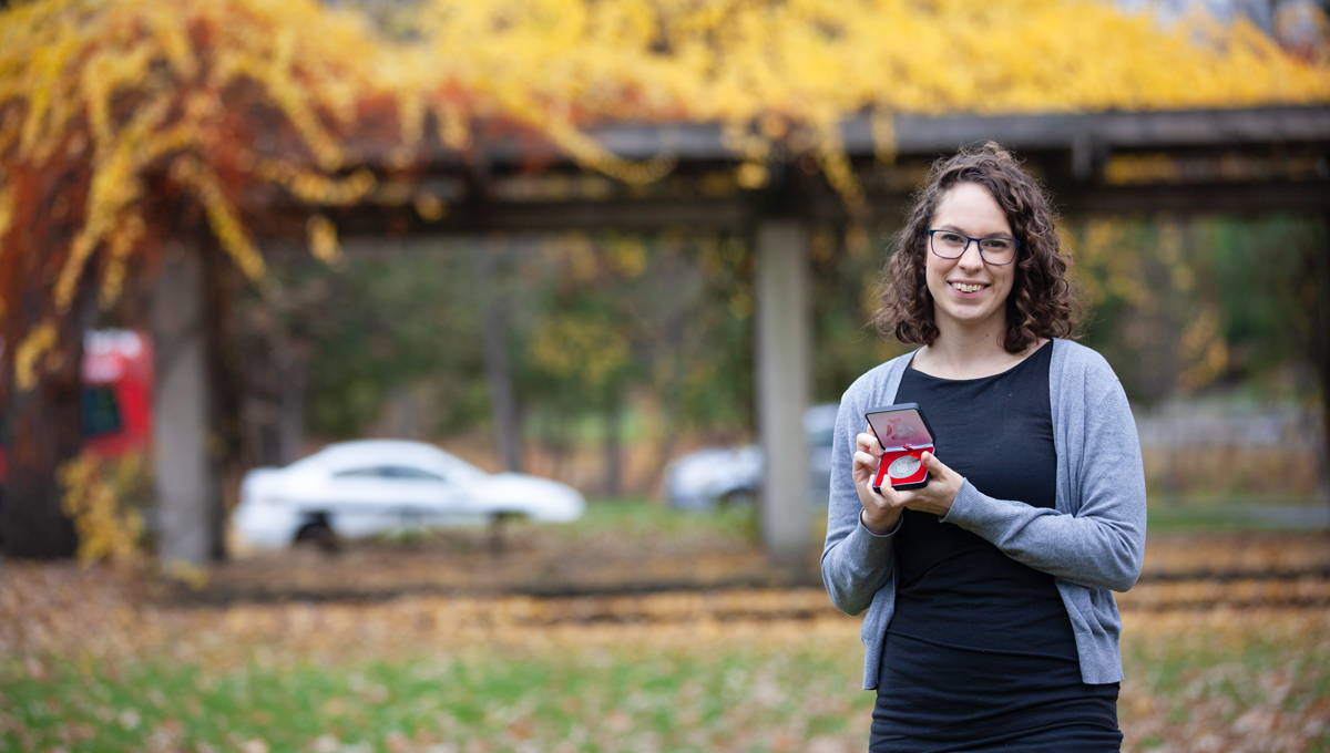 Mercedes Veselka holds her award in Alumni Park with colourful fall trees in the background.