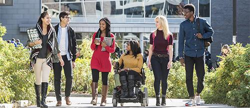 Photo of 6 Carleton University students having a conversation on campus.
