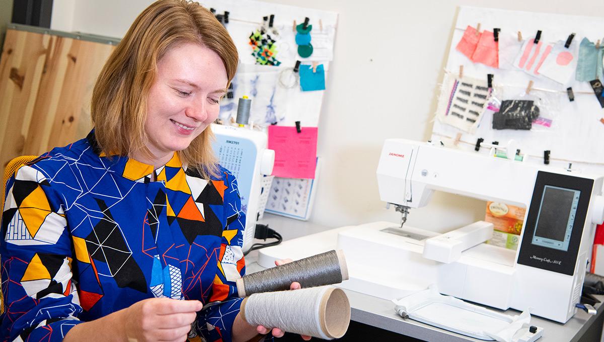 PhD student Lee Jones holding rolls of yarn.
