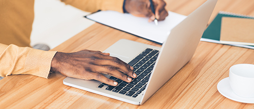 Hands placed on a laptop while another hand writes with a pen on a pad of paper next to the laptop.