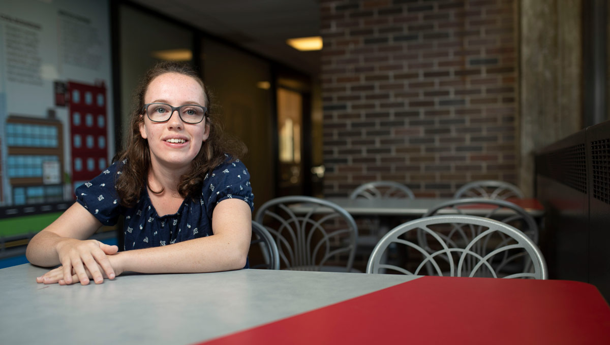 Hannah MacLellan at a table inside the University Centre. Hannah has accomplished a lot at the age of 19 and she's just getting started in her life-long quest for disability rights.