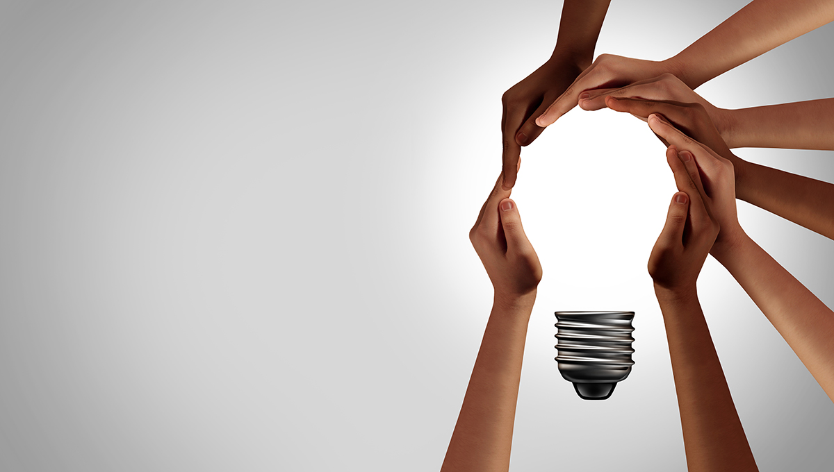 A diverse group of people coming together joining hands into the shape of an inspirational light bulb as a community support metaphor
