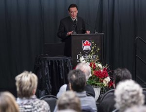 Prof. Martin Kemp speaks at a podium about the Salvator Mundi during the Herzberg Lecture while an audience listens.