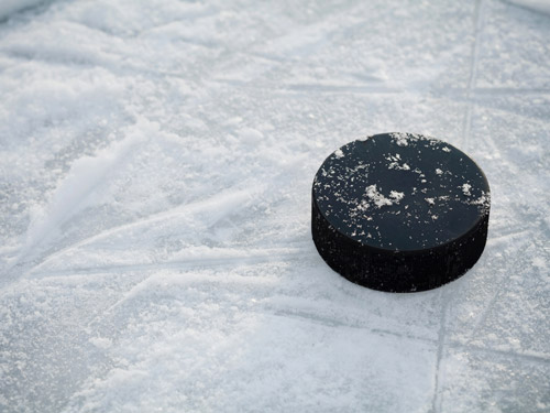 An image of a hockey puck on the ice.