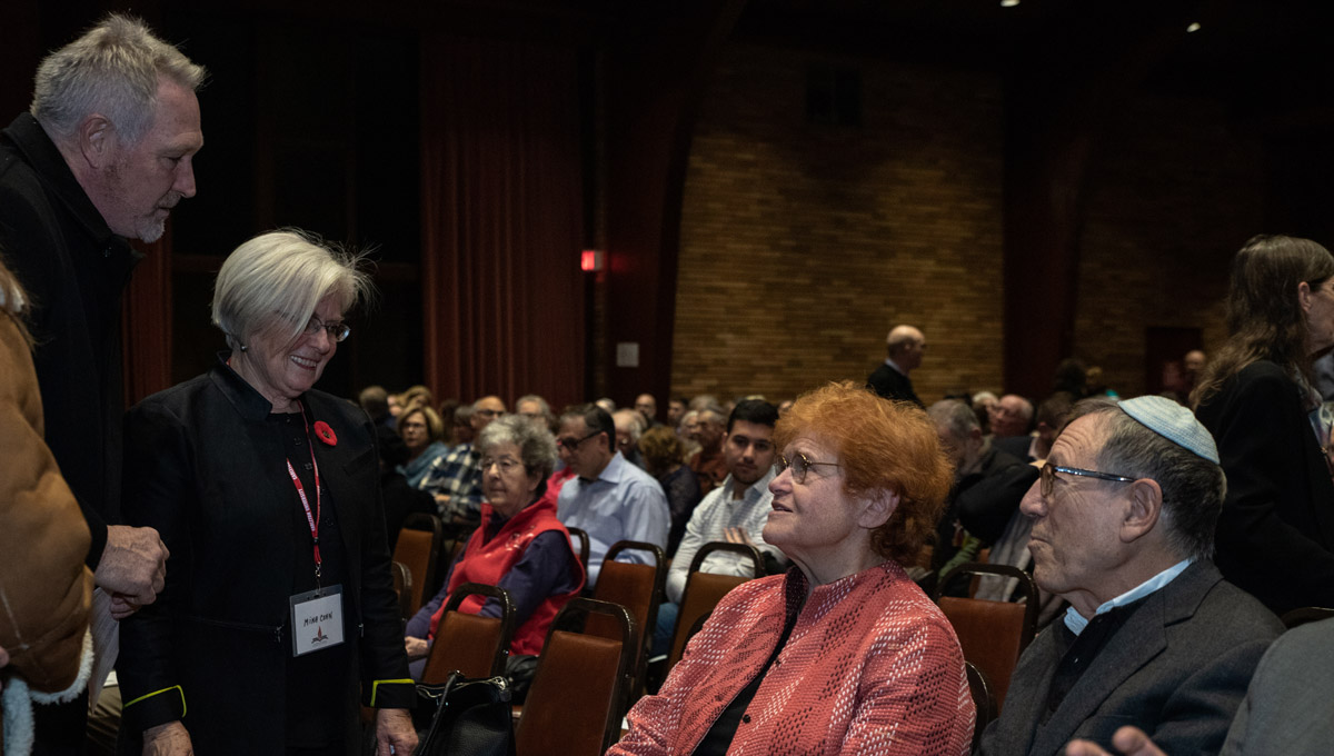 Several standing audience members speak to Deborah Lipstadt, who is seated, after she has finished her lecture.