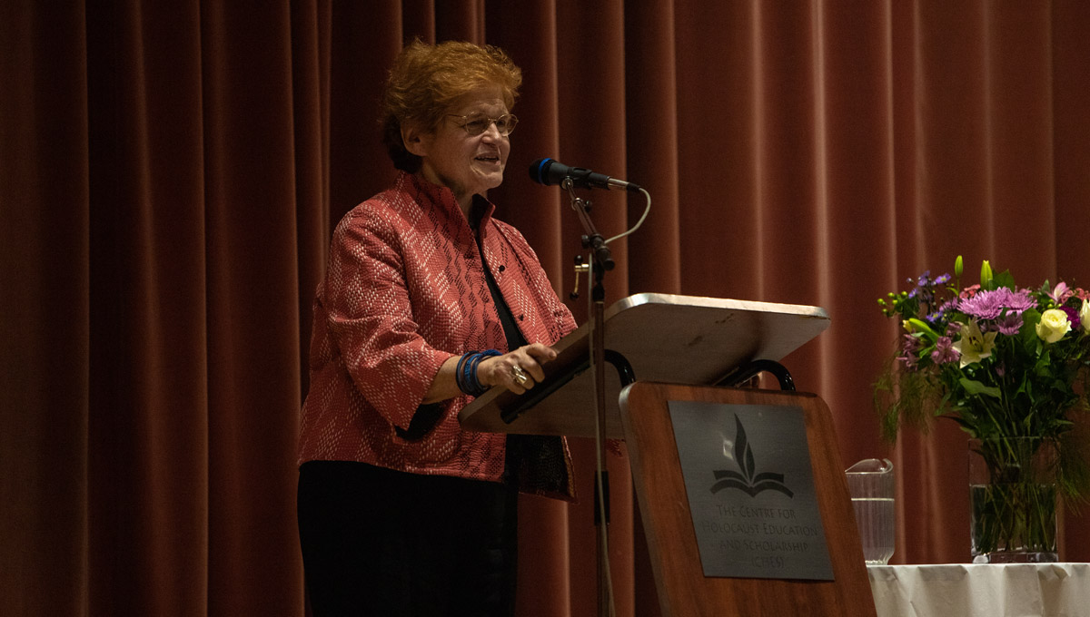 Historian Deborah Lipstadt speaks at a podium while the audience listens.