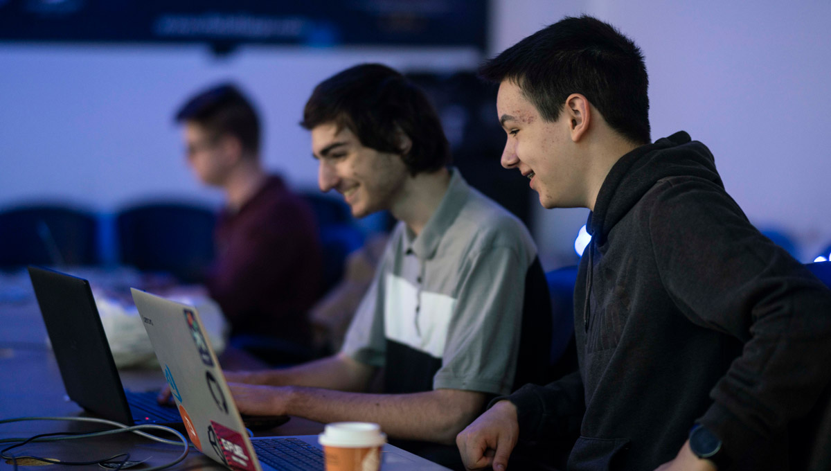 Two competitors type on a laptop while laughing during the iHack event.