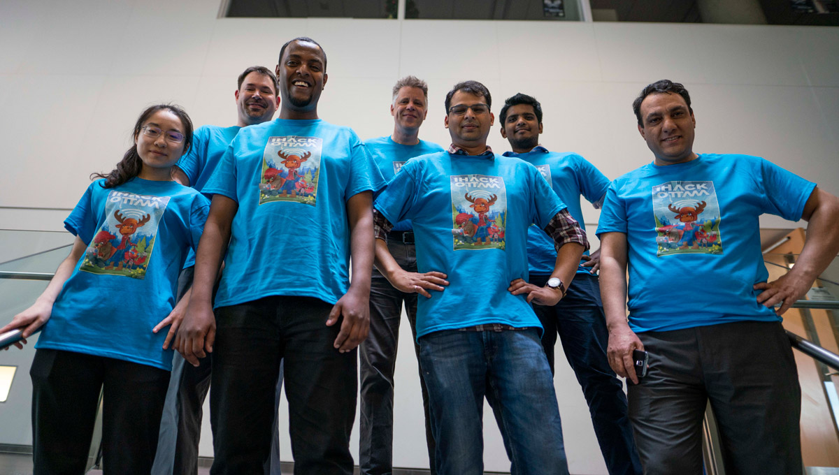 iHack Volunteers in blue T-shirts pose together in Richcraft Hall.