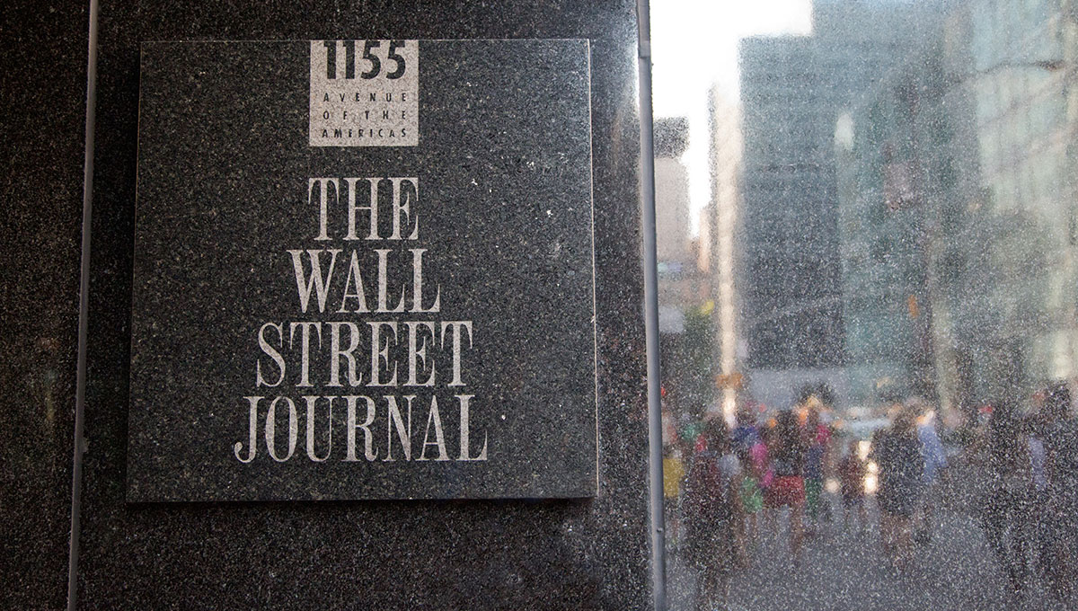 Photo of the sign of The Wall Street Journal outside of its building. At right there are some people and buildings reflected by the marble.