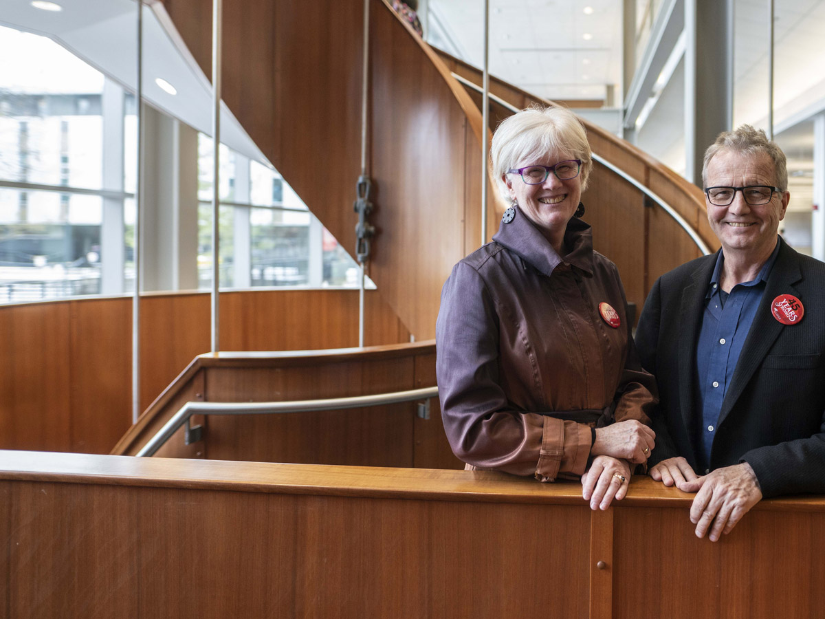 Martha Attridge Bufton and David Dean pose by the spiral staircase in the MacOdrum Library.