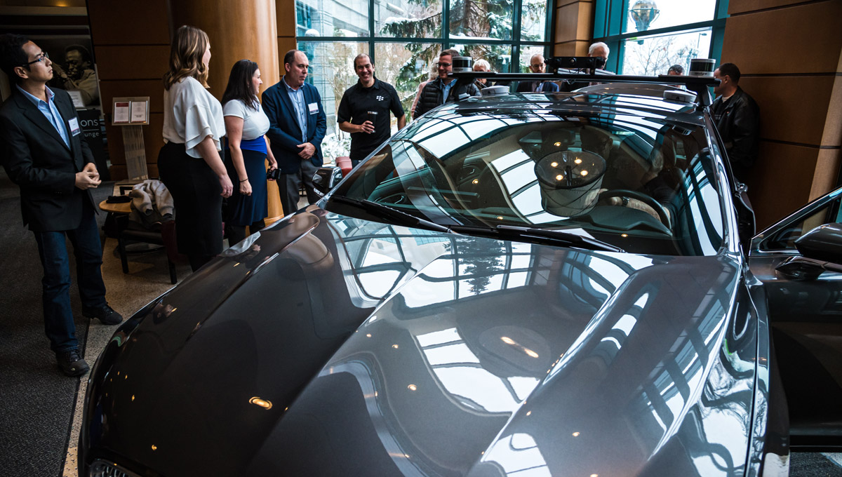 Luncheon goers gather around and inspect a connected and autonomous vehicle in a hotel lobby.