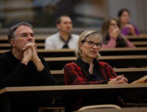 Audience members listen to Elizabeth Abbott speak in an auditorium.
