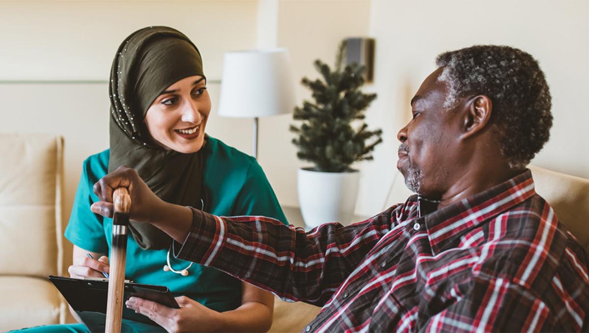 A woman helps an elder man