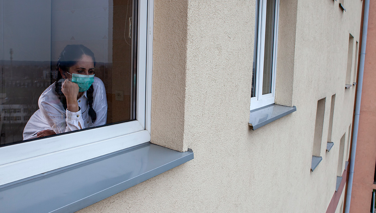 A 40-year-old woman wearing a protective mask is looking out of the window. Home quarantine for 14 days due to the coronavirus COVID-19 epidemic.